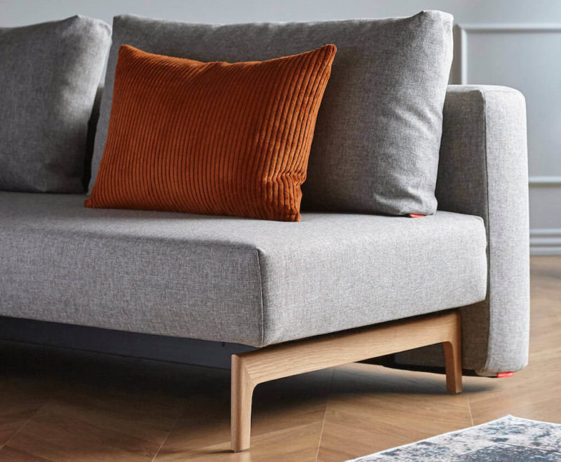 Trym Sleek Sofa Bed in 521 Mixed Grey with an orange cushion