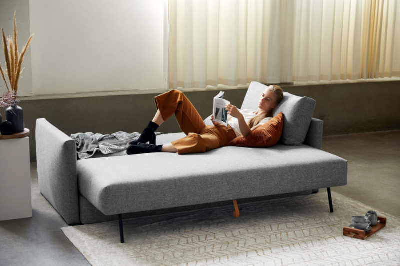 Woman lying down, reading on the Sydney Storage with Arms Sofa Bed opened up as a bed